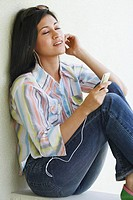 Side profile of a young woman sitting on a ledge listening to an MP3 player