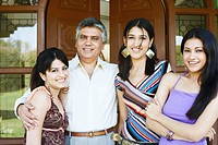 Portrait of a father standing with his three daughters