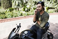 Young man sitting on a motorcycle using a mobile phone