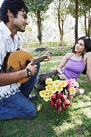 Young man playing the mandolin with a young woman looking at him