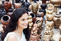 Side profile of a young woman smiling in a pottery store