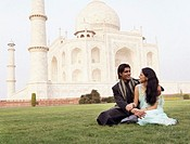 Young couple sitting in front of a mausoleum, Taj Mahal, Agra, Uttar Pradesh, India