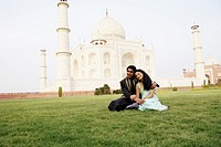 Young couple sitting in front of a mausoleum, Taj Mahal, Agra, Uttar Pradesh, India (thumbnail)