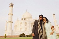 Young couple standing in front of a mausoleum, Taj Mahal, Agra, Uttar Pradesh, India