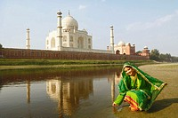 Young woman crouching on the riverbank, Taj Mahal, Agra, Uttar Pradesh, India