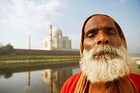 Close-up of a priest meditating with his eyes closed on the riverbank, Taj Mahal, Agra, Uttar Pradesh, India