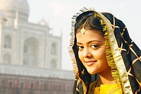 Portrait of a young woman smiling in front of a mausoleum, Taj Mahal, Agra, Uttar Pradesh, India