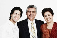 Portrait of a mature couple standing with their son smiling (thumbnail)