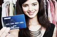 Portrait of a young woman standing in a clothing store holding a credit card