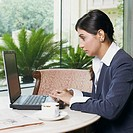 Side profile of a businesswoman working on a laptop