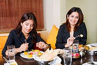 Close-up of two businesswomen eating in a restaurant (thumbnail)