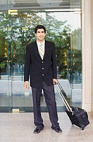 Portrait of a businessman holding a suitcase (thumbnail)