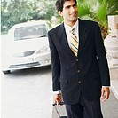 Close-up of a businessman walking with a suitcase (thumbnail)