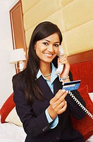 Portrait of a businesswoman talking on the telephone and holding a credit card