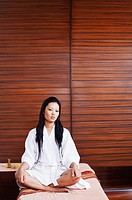 Portrait of a young woman in a bathrobe sitting on a massage table