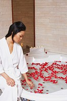 Young woman sitting on the edge of a bathtub and touching rose petals