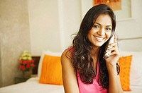 Portrait of a young woman talking on a cordless phone and smiling