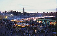 Crowd in street market with mosque in background, Koutoubia Mosque, Marrakesh, Morocco