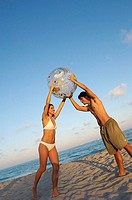 Young couple holding a beach ball