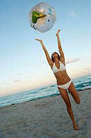 Young woman standing on the beach and tossing a beach ball