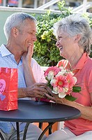 Close-up of a senior couple holding a bouquet of flowers and looking at each other