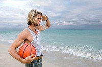 Young man holding a basketball on the beach