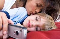 Close-up of a boy holding a mobile phone with his mother behind him