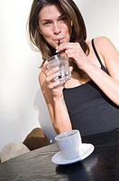 Portrait of a young woman drinking water with a drinking straw