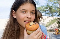 Portrait of a teenage girl eating a muffin