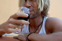 Close-up of a young man drinking red wine