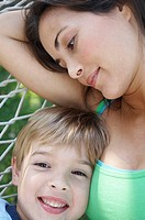Close-up of a mid adult woman and her son lying in a hammock