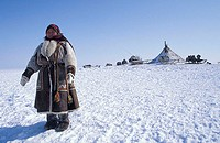 Nentsi nomad woman in traditional clothing, standing before her yurt tent on the tundra west of the arctic Urals, northern Russia