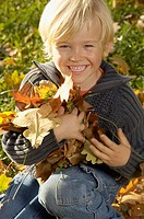Boy holding a pile of leaves