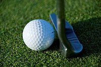 Close view of a putter against a golf ball on the green