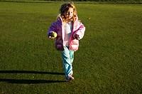 A young girl runs on a golf course