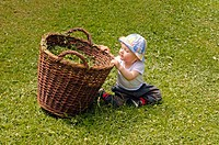 little girl (1 year old) playing with wicker basket at the garden