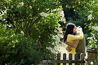 Couple hugging by garden gate