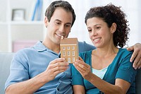 Couple holding a model of a house