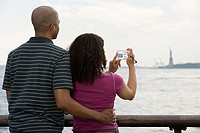 Couple photographing statue of liberty