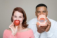 Dentist and woman holding an apple and false teeth