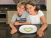 Boy and girl with plate of peas in heart shape