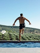 Man jumping into swimming pool