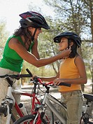 Mother putting bicycle helmet on girl