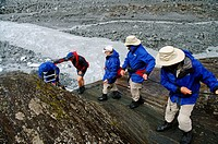 Ecotourists descending from Franz Joseph glacier with help from guide, Westland National Park, New Zealand