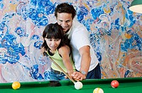 couple playing billiard with painting in the background