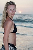 Portrait of a good looking blonde woman next to the ocean in a black bikini and sarong looking at camera with the sun setting