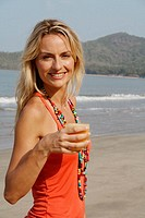 Beautiful blonde woman wearing an orange vest and drinking a glass of orange juice on a beach in India