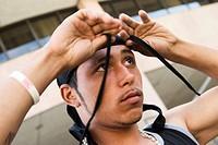 Young Hispanic man putting on a cloth cap