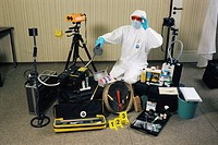 Forensic science equipment  Forensic scientist holding a Mini-CrimeScope 400 light, surrounded by other forensic equipment  This includes a camera upp...