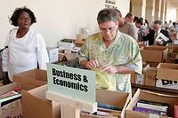Book sale, box, browsing, Black woman, Hispanic, sign, business, economics.  Miami-Dade Public Library. Miami. Florida. USA.